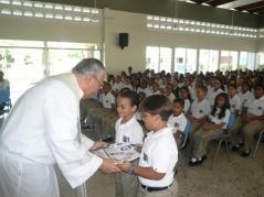 EL P. Rogelio recibiendo las ofrendas de los niños